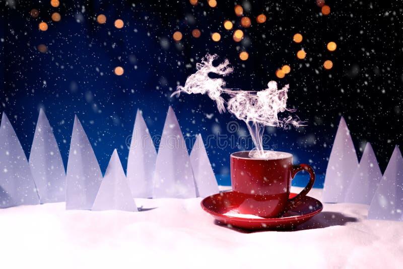 Vapor en reno y Santa Claus en el vuelo de la forma del trineo sobre la taza roja de café o de té en paisaje nevoso La Navidad o  fotografía de archivo libre de regalías