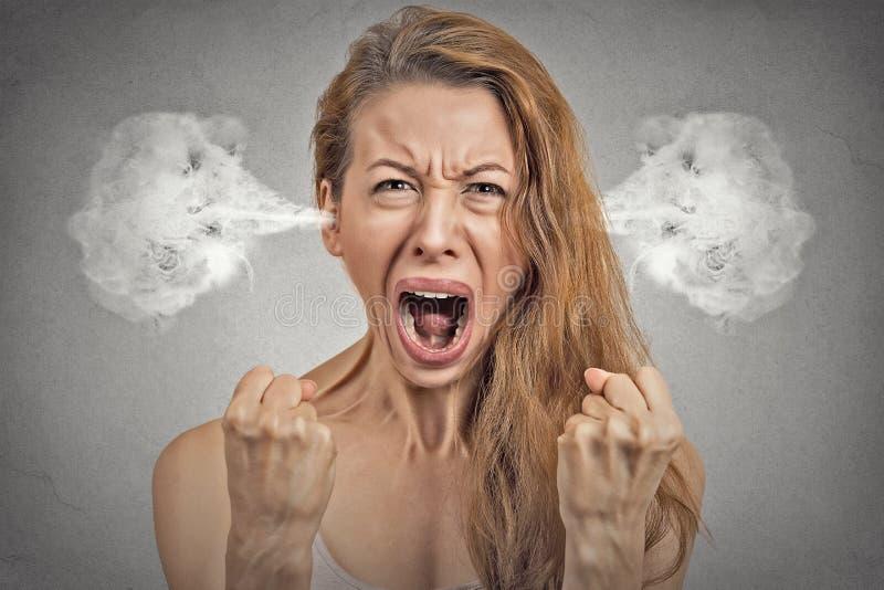 Vapore arrabbiato della giovane donna che esce dalle orecchie che gridano fotografie stock libere da diritti