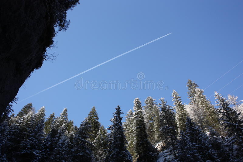Vapour trail through snowy Dolomites stock images