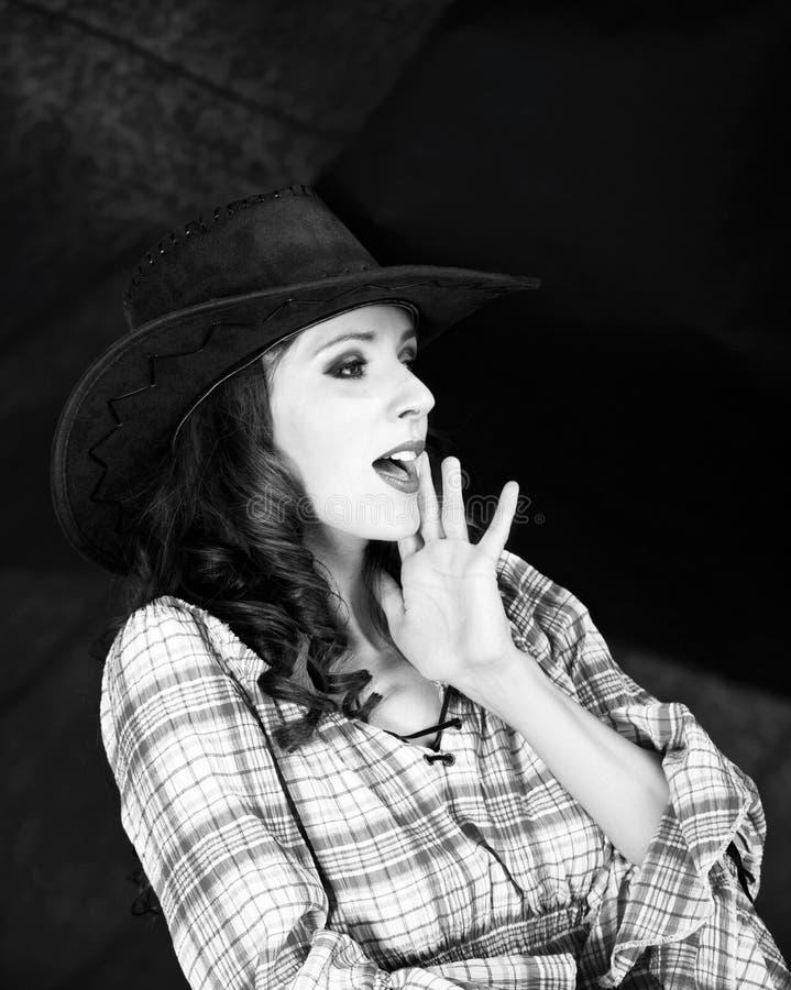 Vaqueira moreno bonita no chapéu de vaqueiro no fundo escuro foto de stock