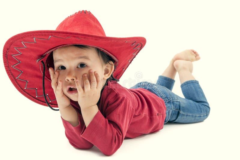 Vaqueira pequena em um chapéu vermelho que levanta em um branco imagens de stock