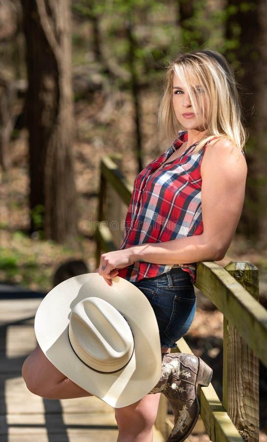 Vaqueira que descansa na cerca com seu chapéu branco da vaqueira imagens de stock royalty free