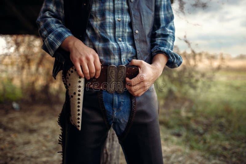 Vaqueiro com sua mão no revólver, oeste selvagem fotografia de stock