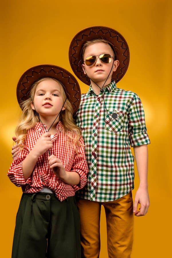 vaqueiro pequeno e vaqueira à moda que levantam nos chapéus, imagens de stock
