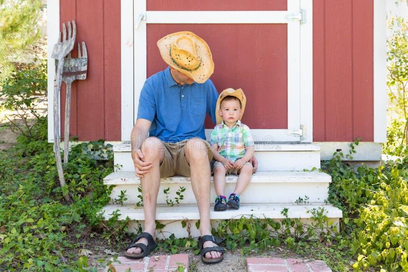 Vaqueiro vestindo Hats do filho chin?s do pai caucasiano novo brincalh?o e da ra?a misturada fotografia de stock royalty free