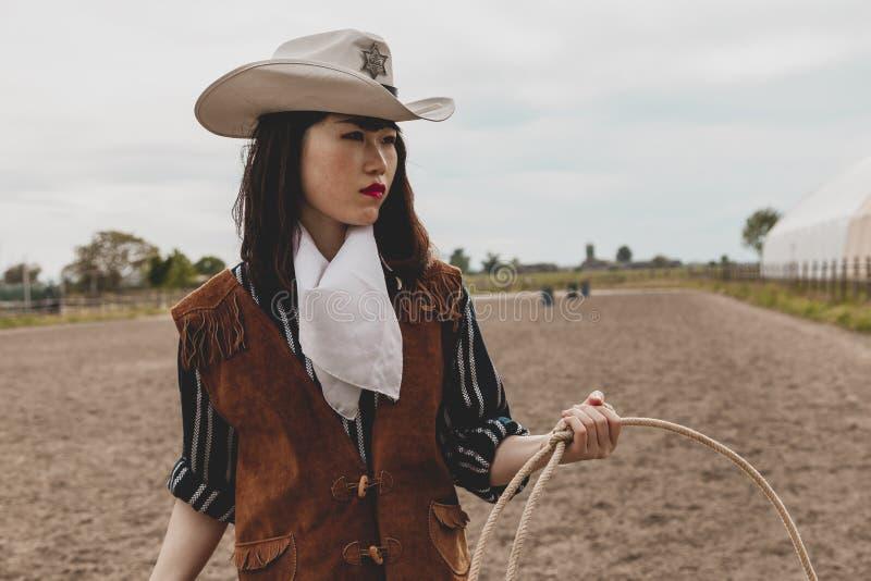 Vaquera china bonita que lanza el lazo en un prado del caballo foto de archivo
