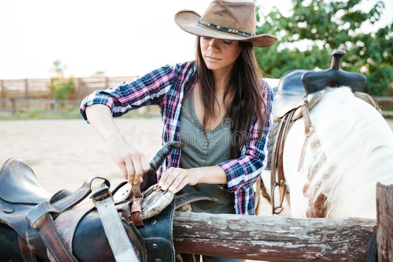 Vaquera de la mujer en el sombrero que prepara la silla de montar para el caballo de montar a caballo imagenes de archivo