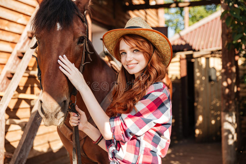 Vaquera feliz de la mujer con su caballo en pueblo foto de archivo libre de regalías