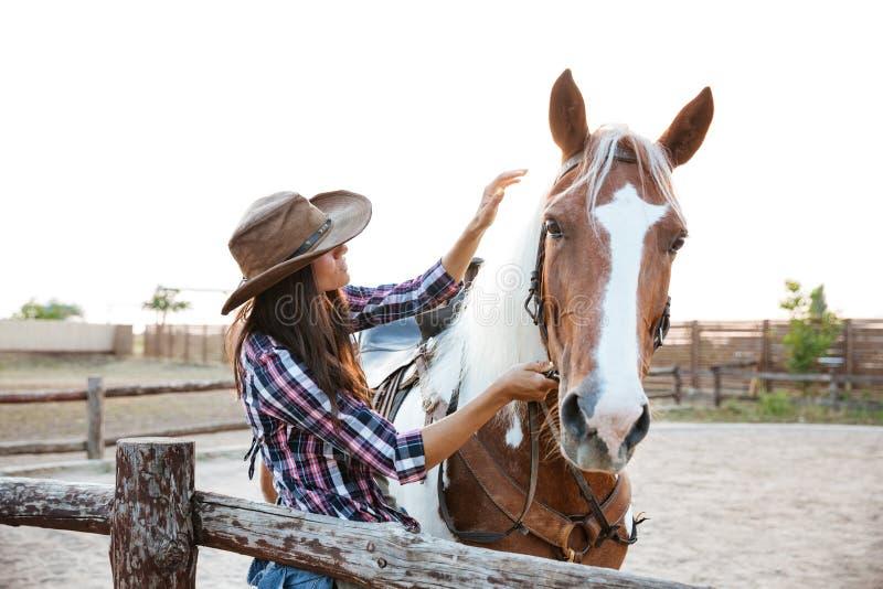 Vaquera hermosa de la mujer joven con el caballo en pueblo fotografía de archivo