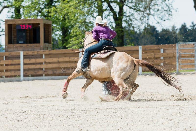 Vaquera joven que monta un caballo hermoso de la pintura en un evento que compite con del barril en un rodeo fotografía de archivo