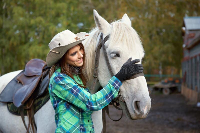 Vaquera sonriente linda con un caballo blanco imagenes de archivo