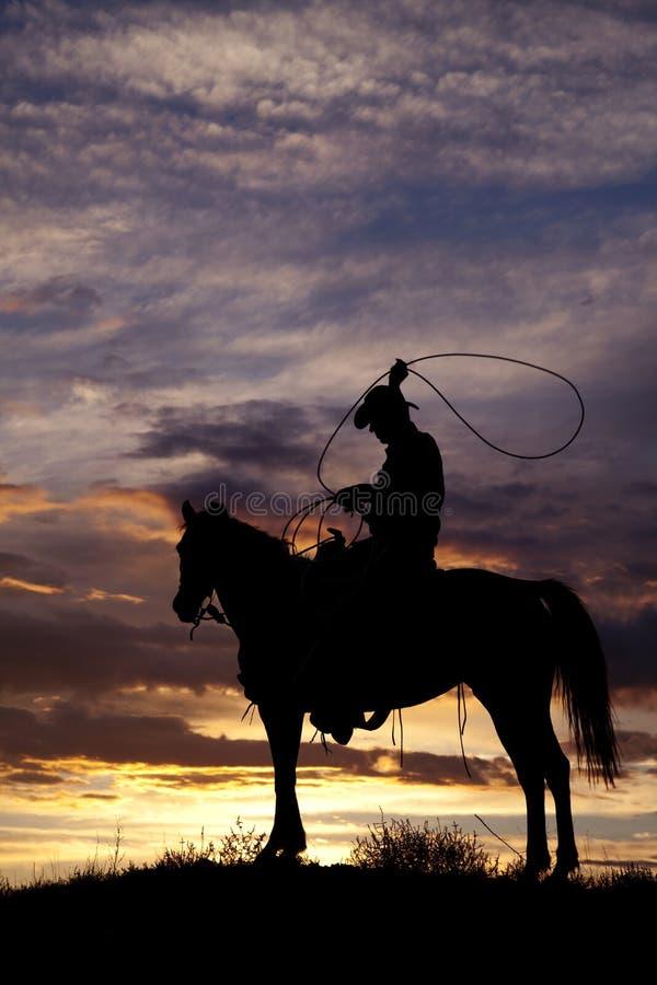 Vaquero en cuerda de balanceo del caballo imagen de archivo