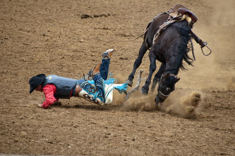 Vaquero que cae apagado un caballo salvaje bucking imagen de archivo libre de regalías