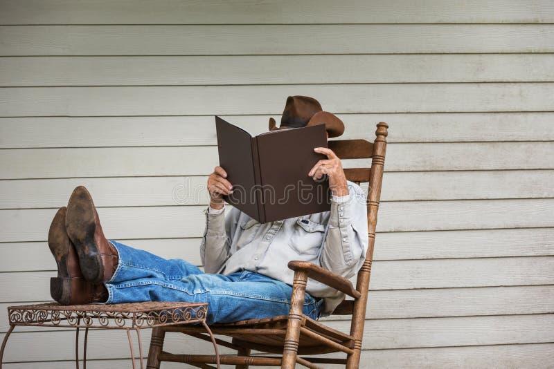 Vaquero Relaxing en el pórtico en mecedora imagenes de archivo