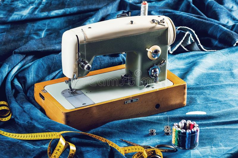 Vaqueros de costura con la máquina de coser, concepto industrial del dril de algodón del añil de la ropa fotografía de archivo