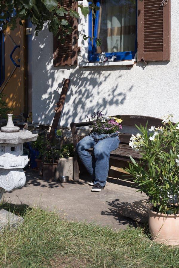 vaqueros del atajo adornados con las flores que se sientan en un banco a del jardín foto de archivo libre de regalías