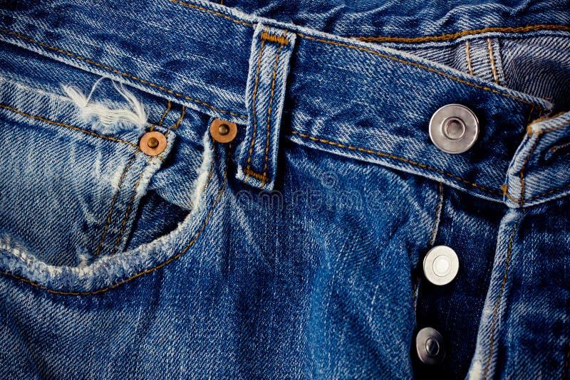 Vaqueros del botón de los vaqueros del fondo del denimand defectuoso y de la plata con una costura de la textura del dril de algo imagen de archivo