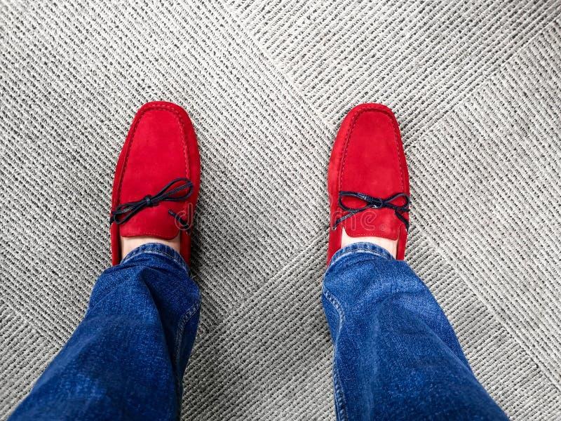 Vaqueros que llevan con los zapatos rojos con clase brillantes del holgazán con los cordones negros imágenes de archivo libres de regalías