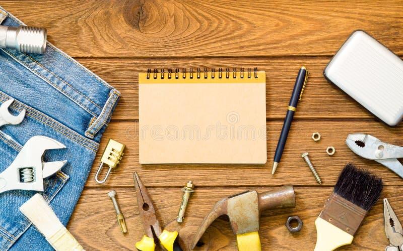 Vaqueros y muchas herramientas prácticas, cuaderno del espacio en blanco en backg de madera foto de archivo