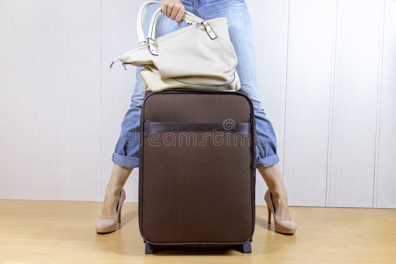 Vaqueros y tacones altos que llevan de la chica joven que se colocan cerca del bolso del equipaje y que sostienen un bolso Concep imagenes de archivo