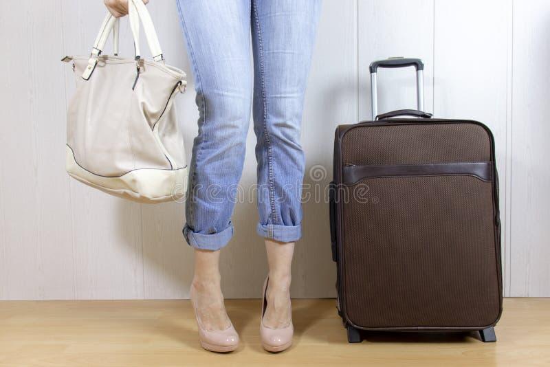 Vaqueros y tacones altos que llevan de la chica joven que se colocan cerca del bolso del equipaje y que sostienen un bolso Concep foto de archivo libre de regalías