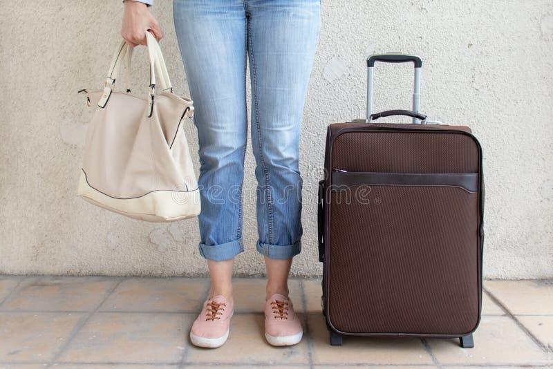 Vaqueros y zapatillas de deporte que llevan de la chica joven que se colocan cerca del bolso del equipaje y que sostienen un bols fotografía de archivo
