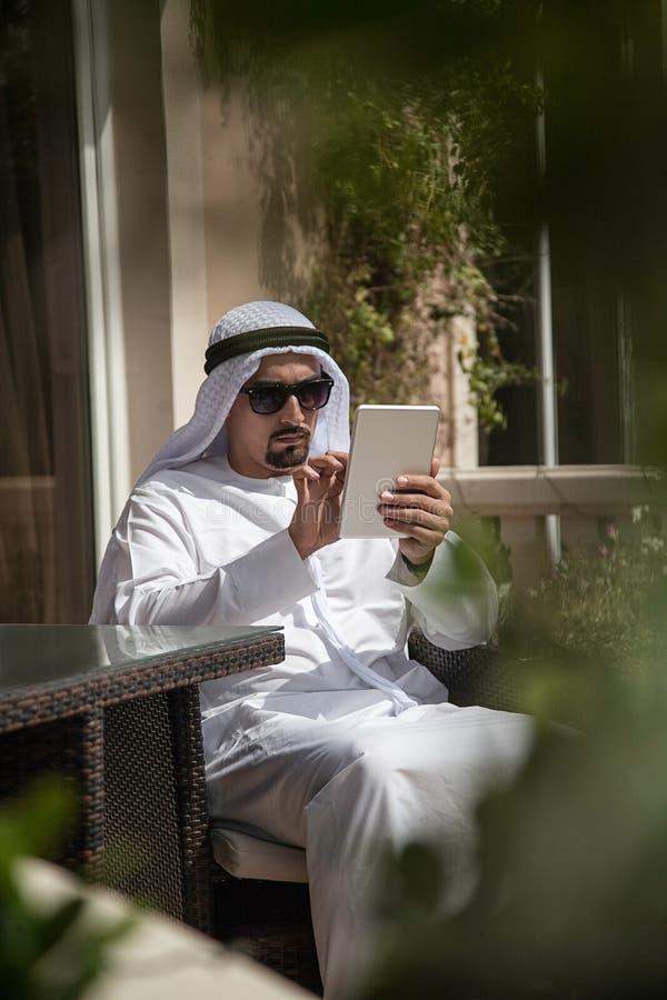 Varón árabe usando Phone Out elegante imagen de archivo