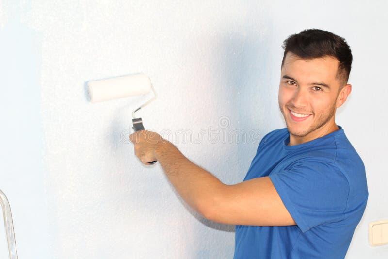 Varón étnico alegre que pinta una pared con un rodillo y una sonrisa imagen de archivo libre de regalías