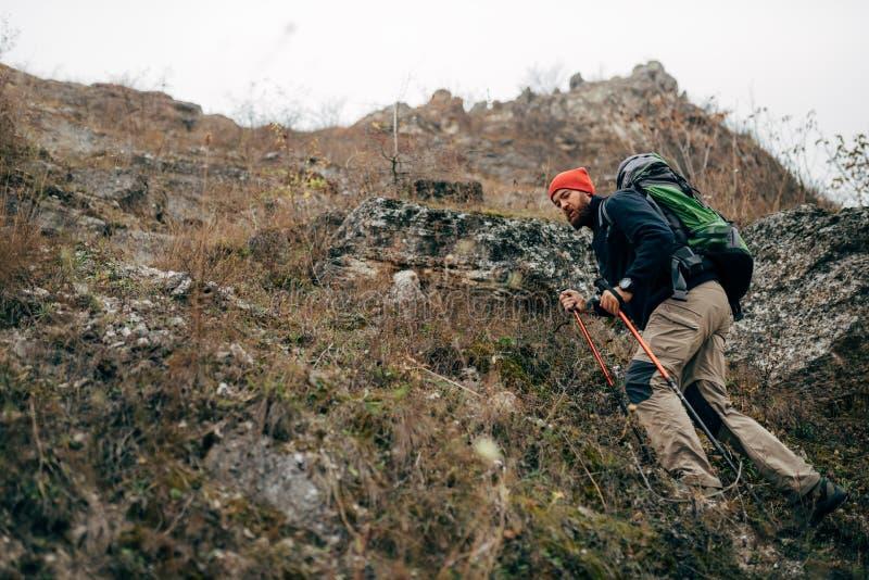 Varón activo joven que camina en montañas con la mochila del viaje Senderismo y alpinismo barbudos del hombre del viajero durante imágenes de archivo libres de regalías