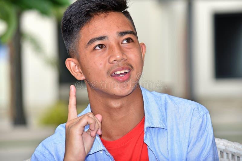 Varón adolescente asiático que tiene una idea imagen de archivo