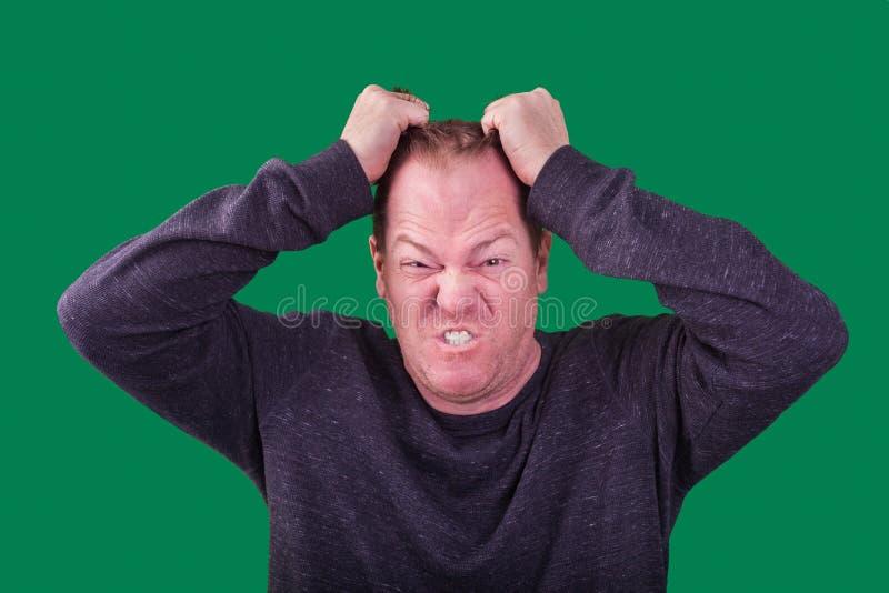 Varón adulto que tira de su expresión facial frustrada enojada del pelo fotografiada en el contexto verde de la pantalla foto de archivo libre de regalías