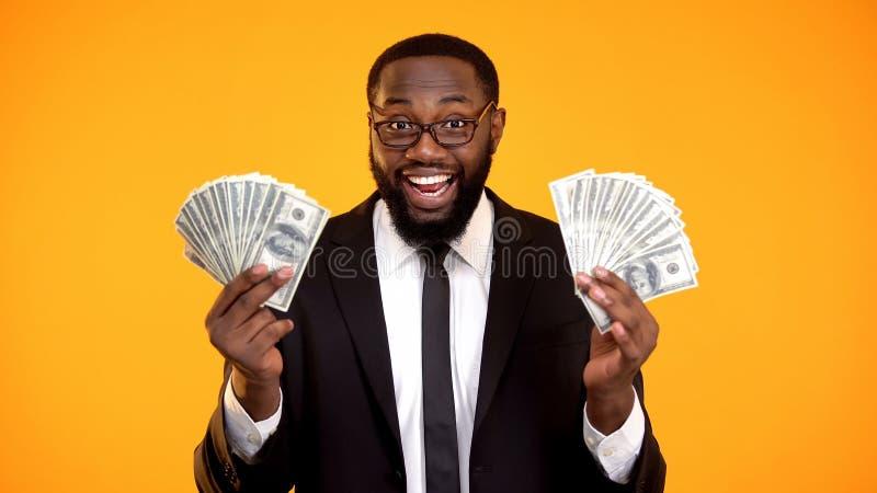 Var?n afroamericano feliz en el traje de negocios que muestra los manojos de efectivo del d?lar, beneficio imagenes de archivo