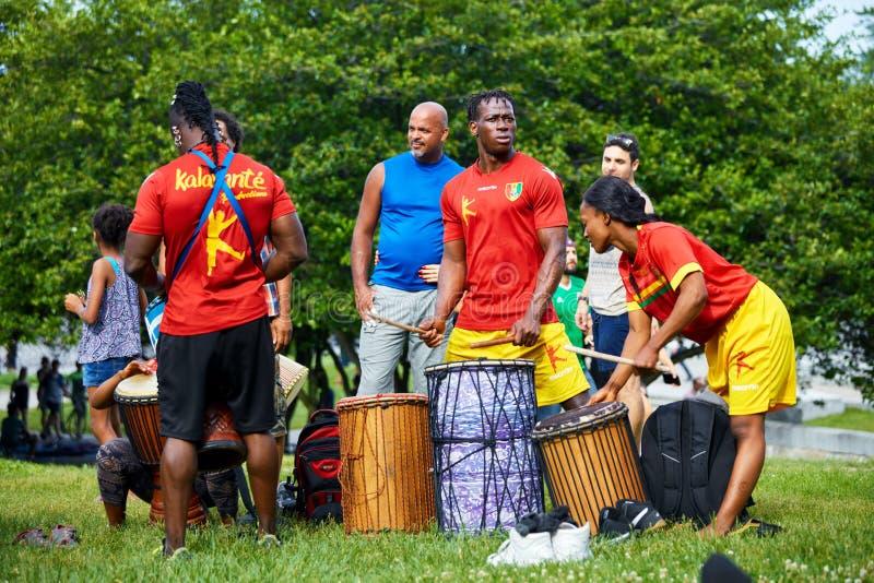 Varón afroamericano y percussionists femeninos que juegan los tambores del djembe y del dunun en el festival de Tam Tams en parqu fotografía de archivo libre de regalías