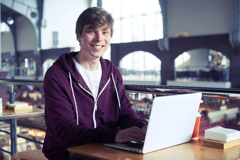 Varón agradable que sonríe mientras que practica surf en ordenador portátil fotografía de archivo libre de regalías