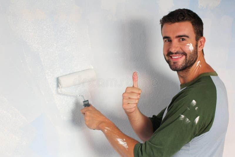 Varón alegre que pinta una pared con un rodillo y un donante manos para arriba fotografía de archivo