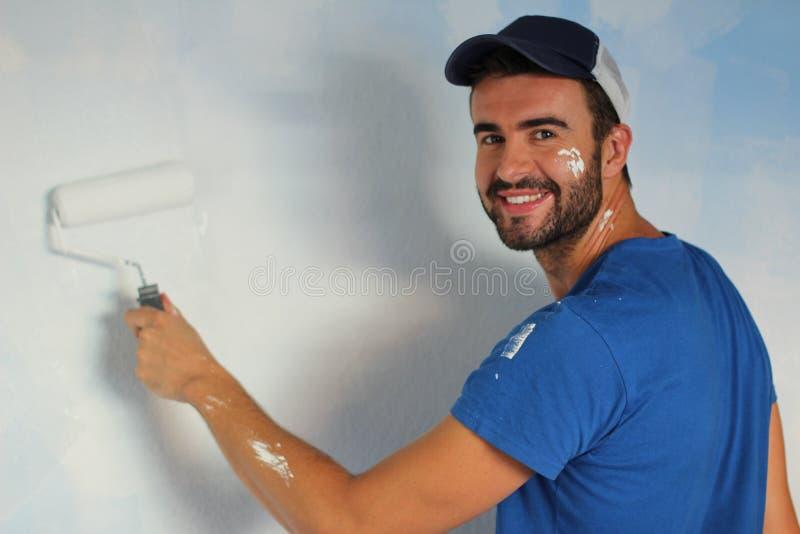 Varón alegre que pinta una pared con un rodillo y una sonrisa fotografía de archivo