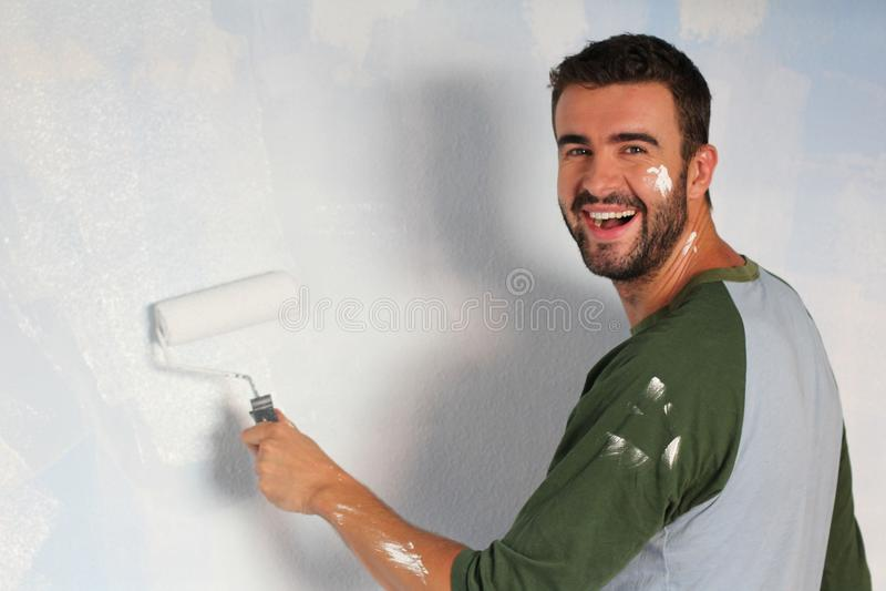 Varón alegre que pinta una pared con un rodillo y una sonrisa fotografía de archivo libre de regalías