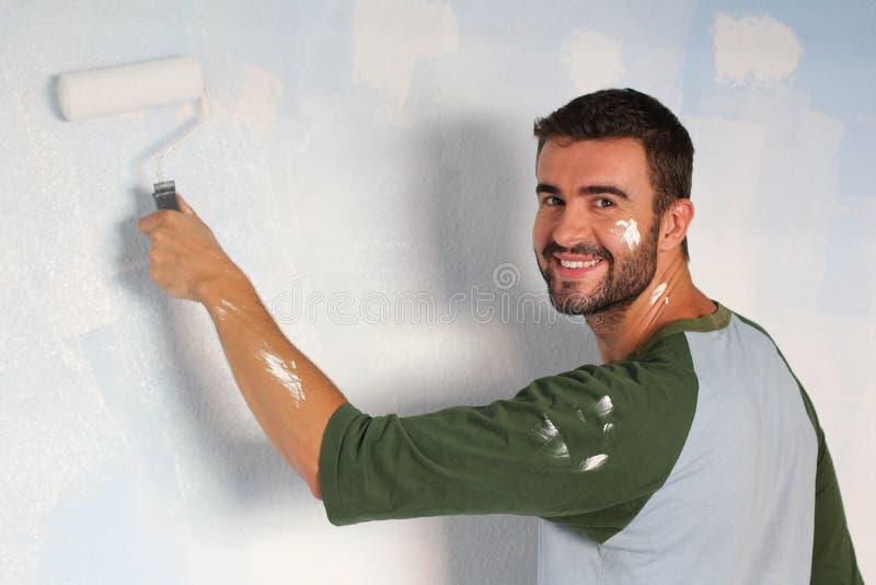 Varón alegre que pinta una pared con un rodillo y una sonrisa foto de archivo libre de regalías