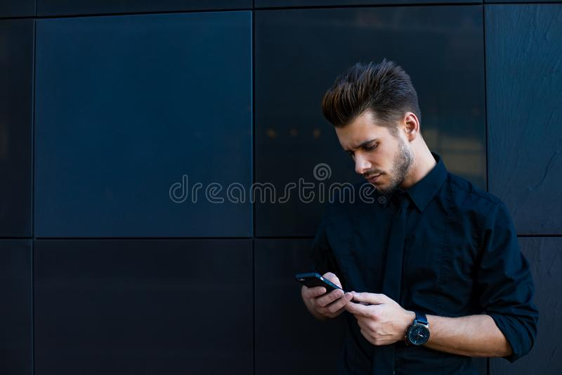 Varón alegre que tiene conversación del teléfono móvil durante resto al aire libre imagen de archivo libre de regalías