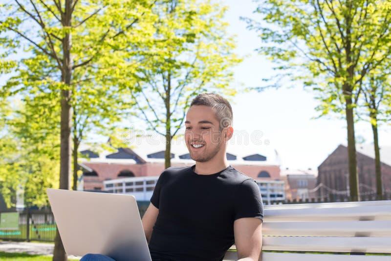 Varón alegre que tiene trabajo de la distancia sobre el ordenador portátil durante resto al aire libre imágenes de archivo libres de regalías