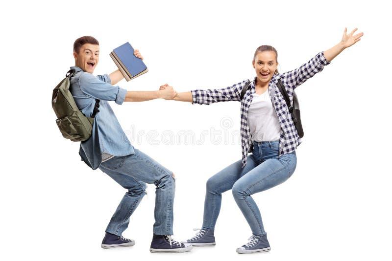 Varón alegre y estudiantes que llevan a cabo las manos foto de archivo