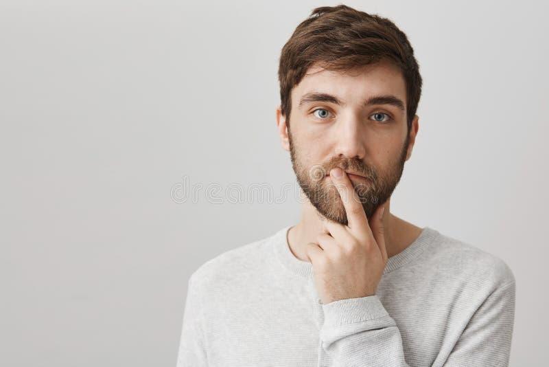 Varón apuesto atento y tranquilo con la barba que lleva a cabo el dedo índice sobre boca y la situación sobre fondo gris fotos de archivo libres de regalías