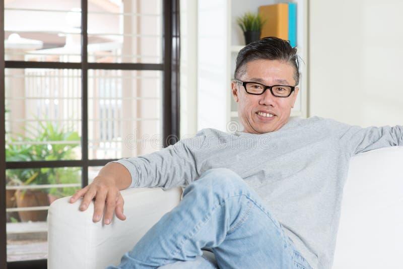 Varón asiático maduro que se sienta en casa fotos de archivo libres de regalías