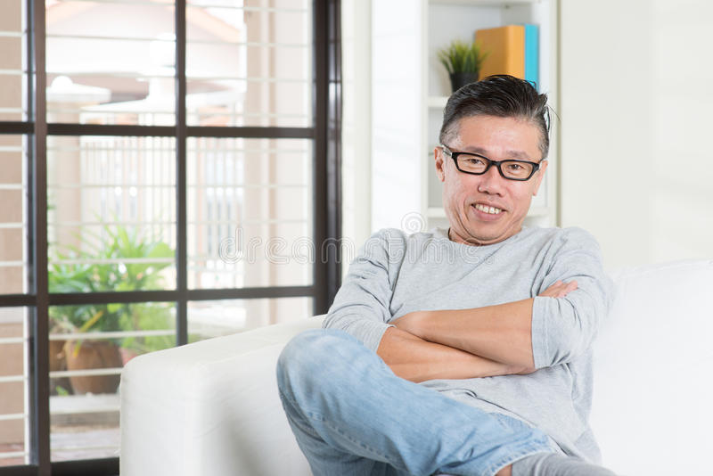 Varón asiático maduro 50s que se sienta en casa imagenes de archivo