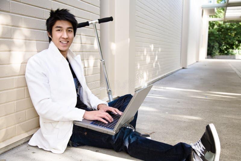 Varón asiático ocasional joven con la computadora portátil imágenes de archivo libres de regalías