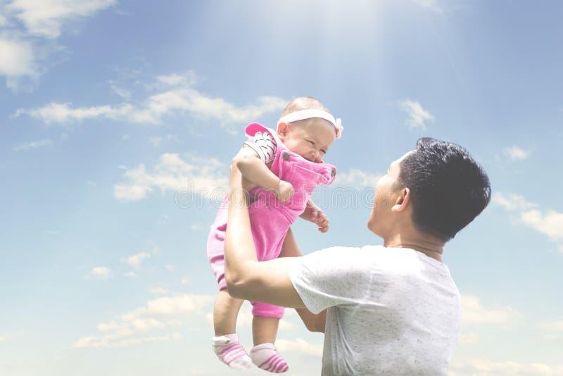 Varón asiático que lanza a su bebé en el cielo fotos de archivo