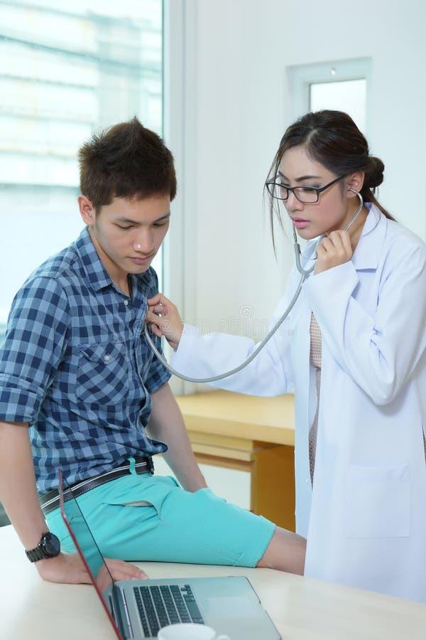 Varón auscultating del doctor de la mujer joven con el estetoscopio fotos de archivo libres de regalías