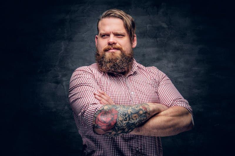 Varón barbudo con los brazos cruzados tatuados imagen de archivo