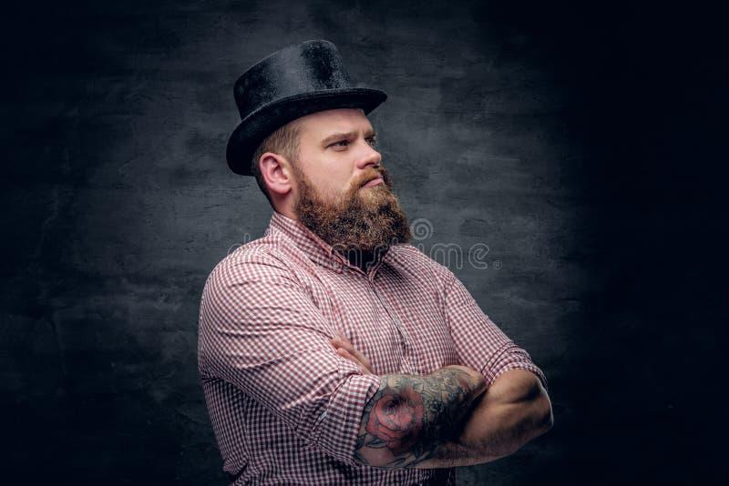 Varón barbudo con los brazos tatuados cruzados fotografía de archivo