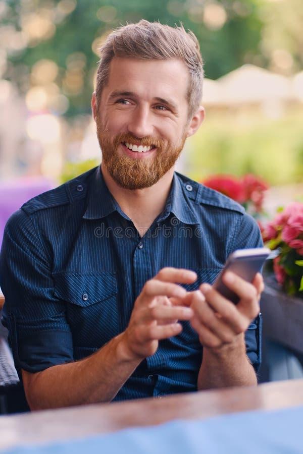 Varón barbudo del pelirrojo positivo usando un smartphone fotos de archivo